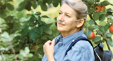 Lady with an oxygen mask picking apples
