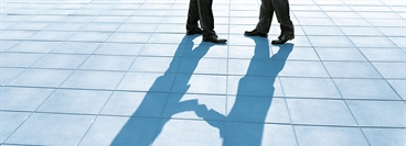 Shadow of buisnessmen shaking hands. Bluish version of ID 103928.