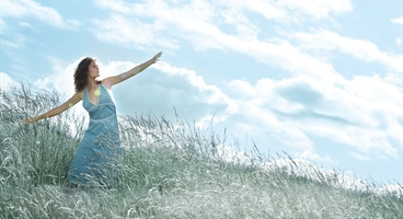 Woman standing a meadow viewing aginst cloudy sky. size 50 x 70 cm portrait. A5 formate. Should symbolize the various environmental applications Specialty gases can offer.